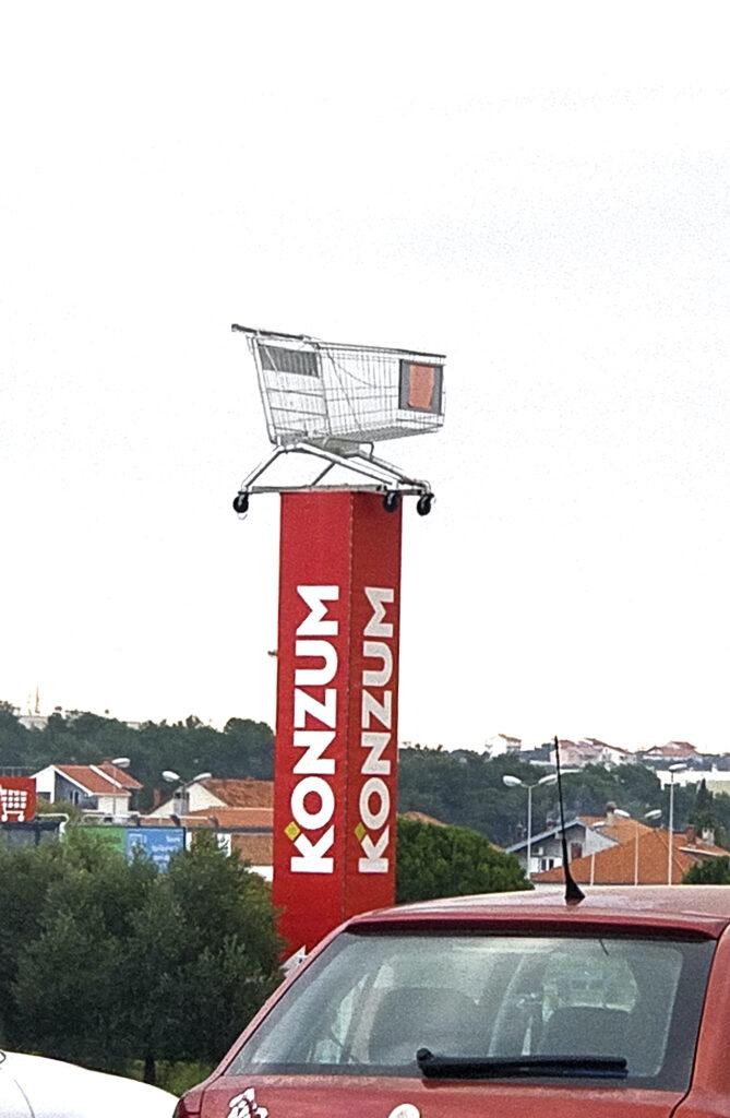 Punaisen korkean mainospylvään päälle nostettu tyhjä ostoskärry