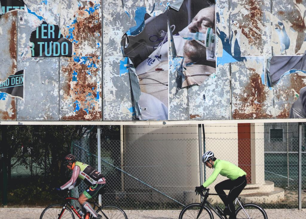 Suurimmaksi osaksi repeytynyt isokokoinen mainos. Etualalla kaksi pyöräilyasusteisiin pukeutunutta miestä pyöräilee.