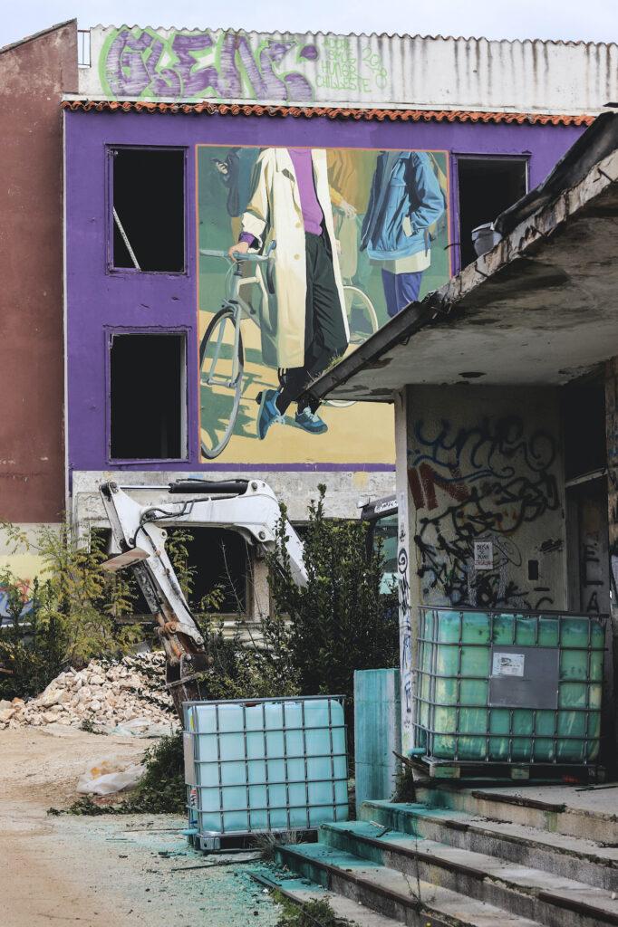 Hylätty talo jonka seinässä on pyörää pitävää henkilöä esittävä muraali. Etualalla kaivinkone ja turkoosiksi spraymaalilla maalaattuja vesitankkeja.