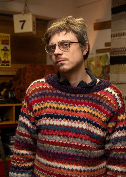 Keskitalo katsoo kameraan, päällään värikäs villapaita.