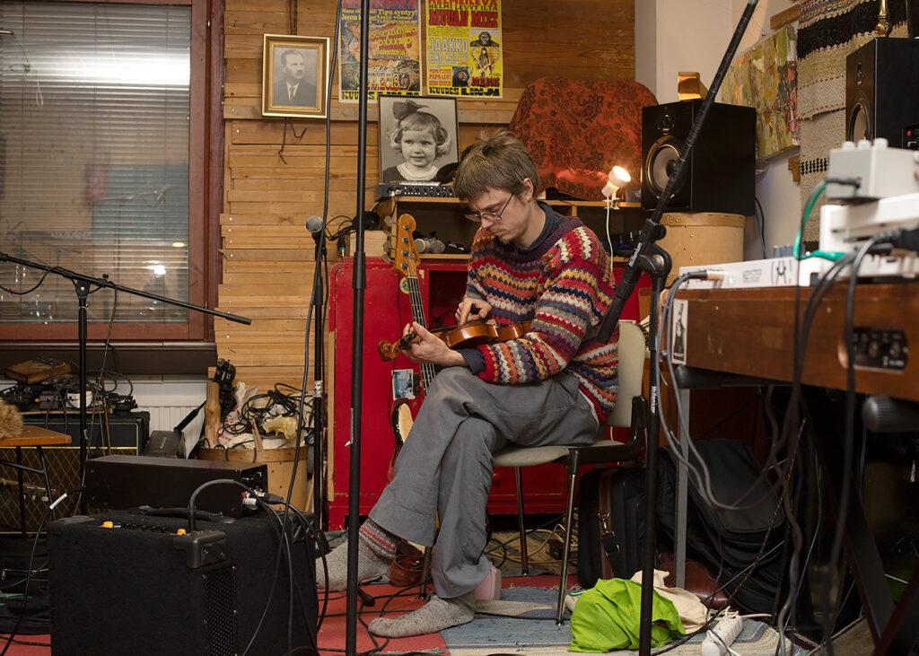 Keskitalo istuu soittimien keskellä sisätilassa. Katsoo käsissään pitelemäänsä viulua.