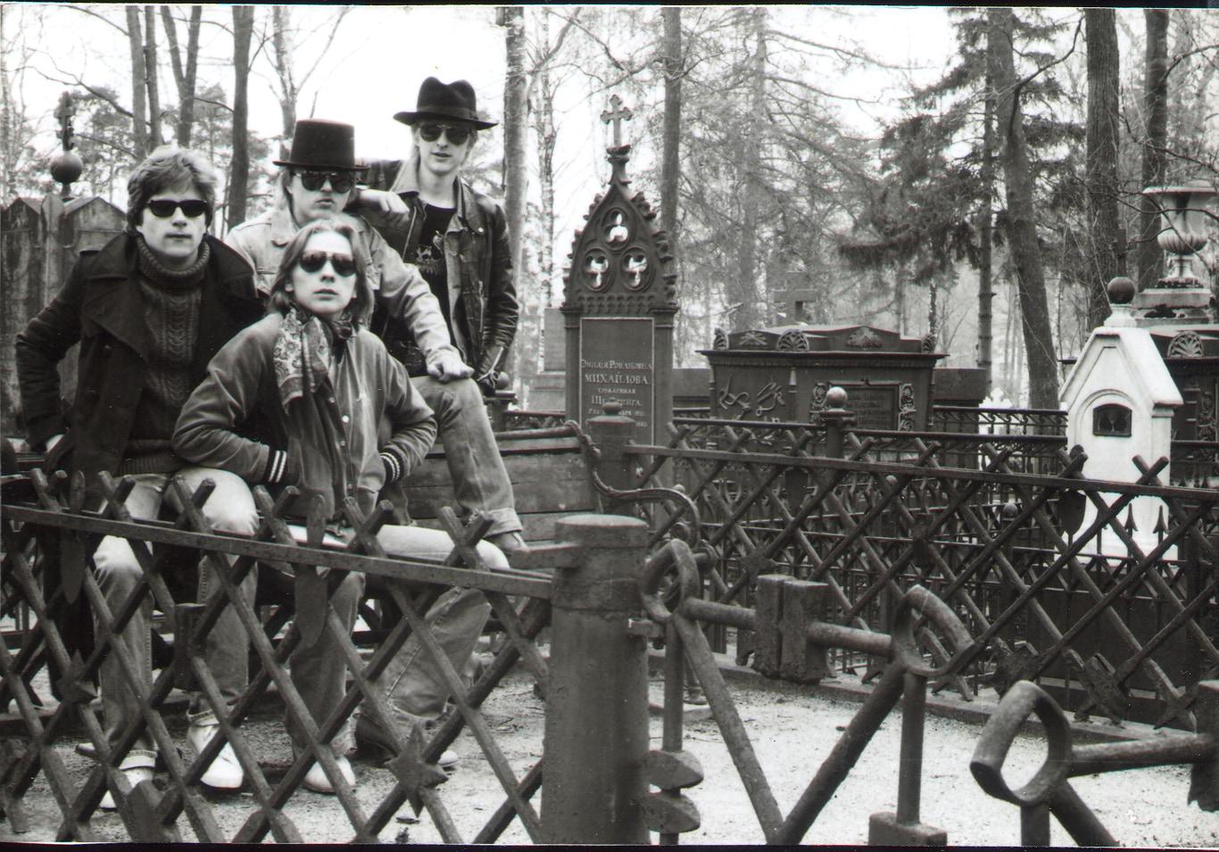 Mustavalkoinen kuva. Neljä muusikkoa aurinkolasit päällä nojaamassa aitaan keskellä hautausmaata.