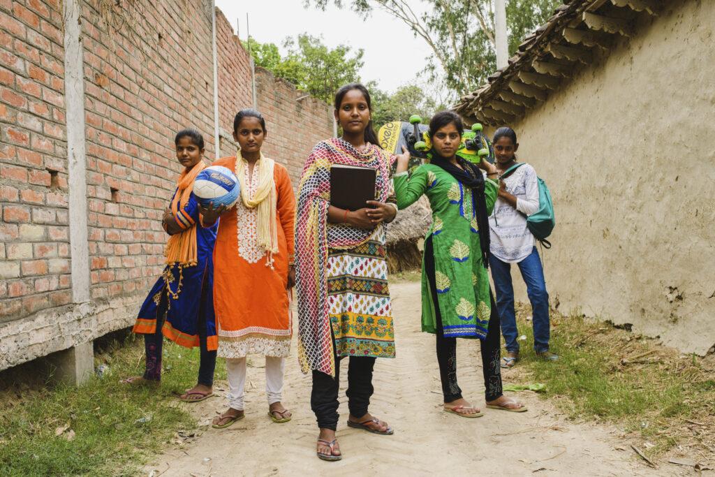 Viisi nuorta seisovat rivissä, käsissään esimerkiksi pallo, skeittilauta ja kirja.