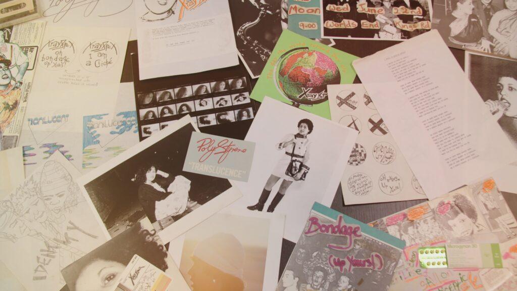 Poly Styreneen liittyviä valokuvia, julisteita, tekstejä, papereita pöydällä.