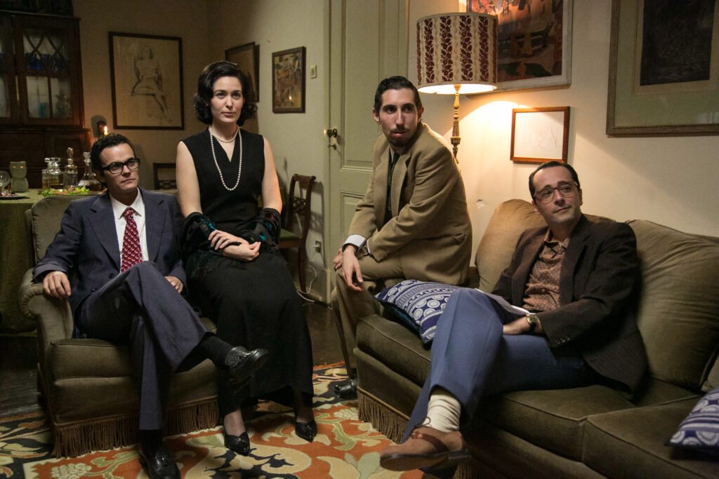 Neljä henkilöä istuu olohuoneessa.