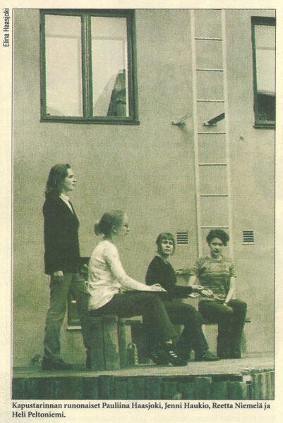 Neljä henkilöä istuu talon edustalla.