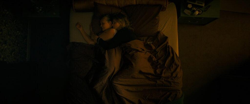 Kaksi naista makaa sängyssä, toinen halaa toista.