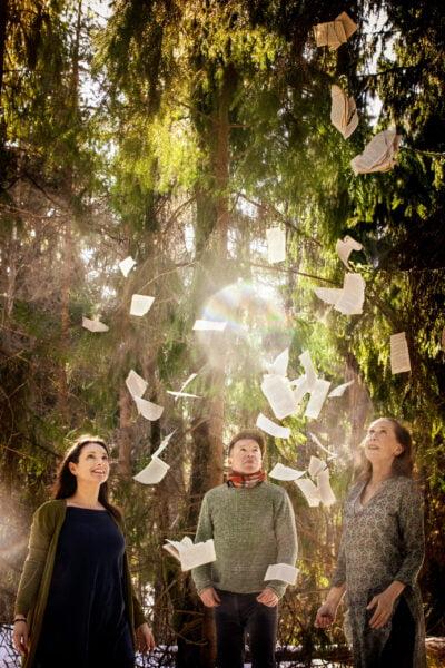 Kuva Laskeutuu lempeä valo -esityksestä. Papereita leijuu ilmassa näyttelijöiden keskellä.