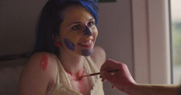Sinitukkainen hymyilevä nainen, jota maalataan eri värein