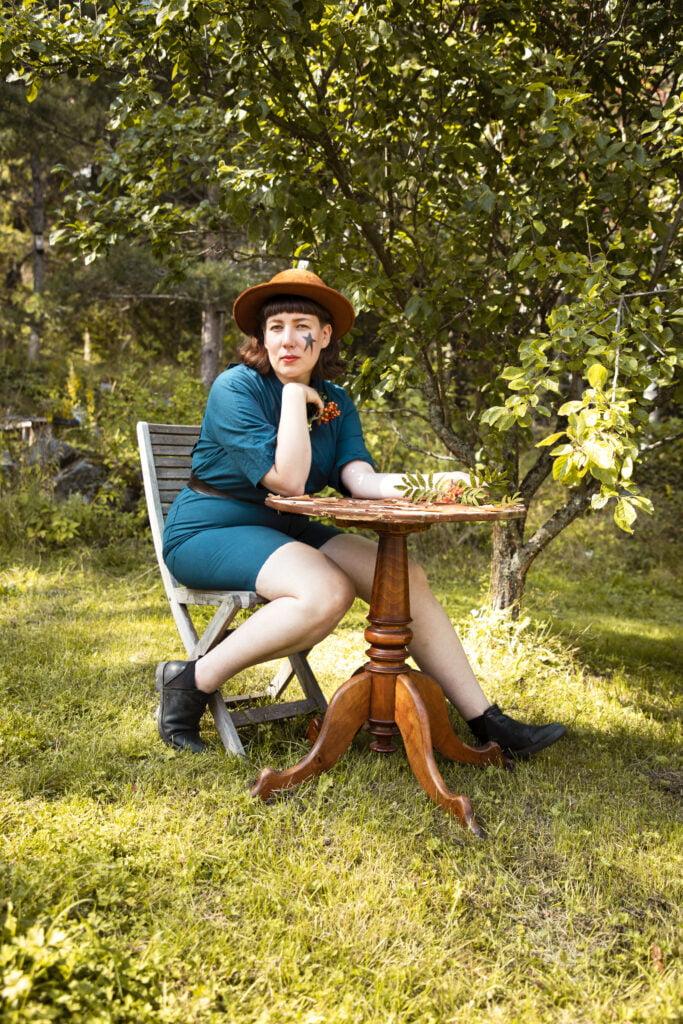 Klemetti istuu pöydän äärellä aurinkoisessa puutarhassa.