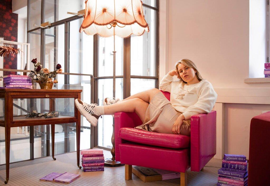 Tanskanen istuu tuolilla, ympärillä kirjoja.