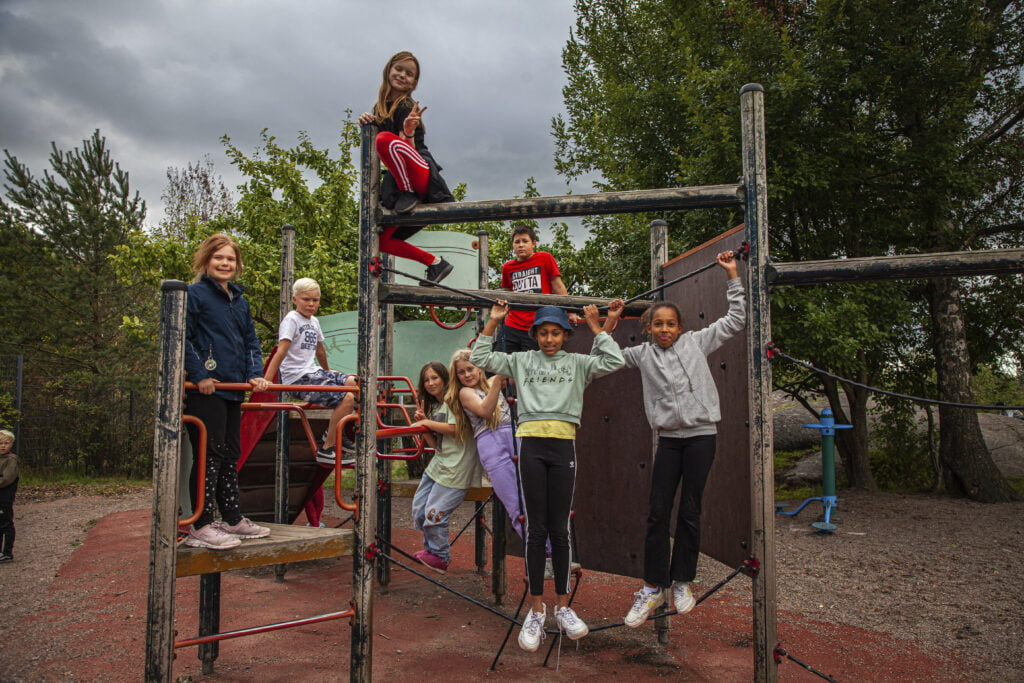 Joukko lapsia poseeraa kiipeilytelineessä.