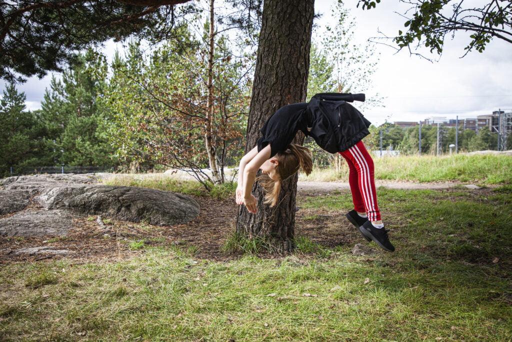 Lapsi hyppää siltakaatoon, taustalla kalliota ja puita.