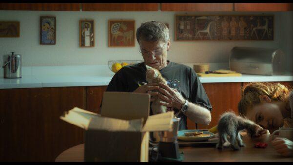 Mies istuu pöydän ääressä pienen kissanpennun kanssa